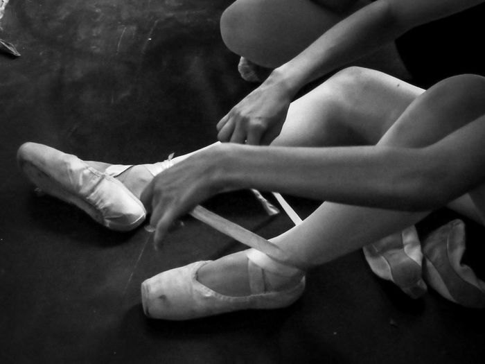 Low section of woman wearing ballet shoes