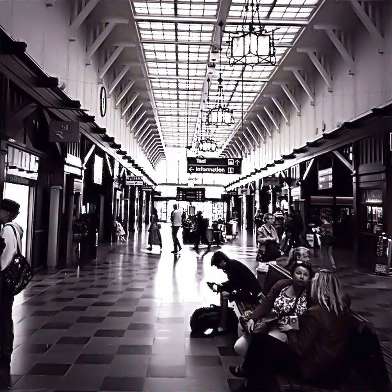 transportation, real people, indoors, public transportation, ceiling, large group of people, men, travel, train - vehicle, mode of transport, walking, sitting, rail transportation, architecture, railroad station, railroad station platform, architectural column, lifestyles, day, journey, built structure, transportation building - type of building, women, luggage, people