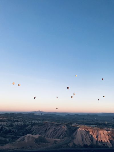 Hot air balloons flying over landscape against sky during sunset