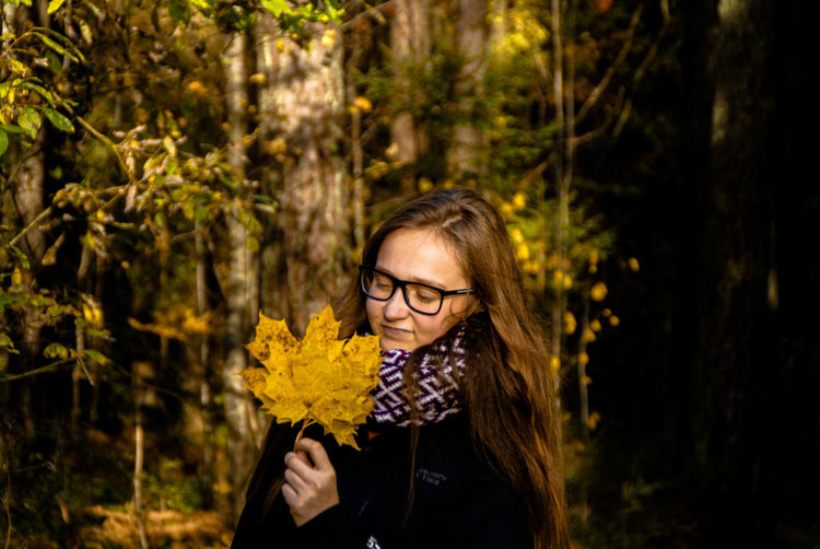 Close-up of young woman holding autumn leaves