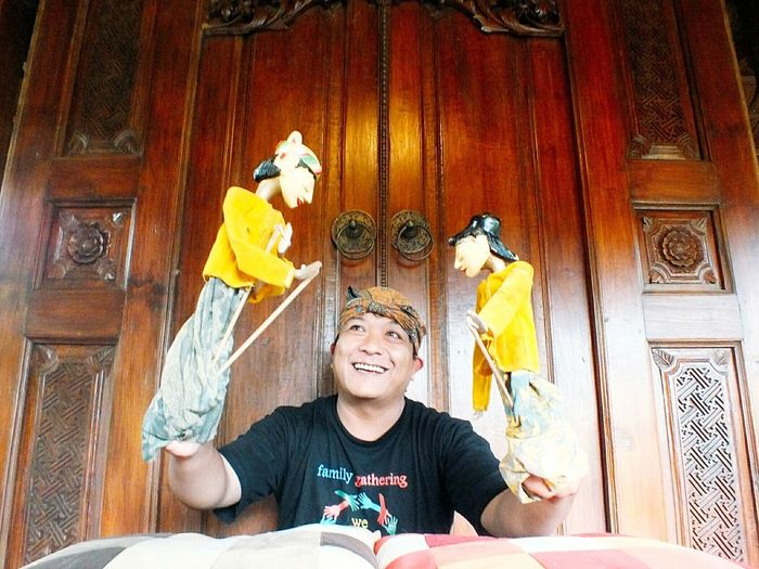 Happy Young Man Showing Puppet Show Against Closed Door
