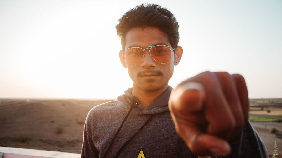 Glasses One Person Sky Front View Real People Portrait Young Men Lifestyles Young Adult Leisure Activity Nature Headshot Focus On Foreground Casual Clothing Sunglasses Land Holding Eyeglasses  Looking At Camera Fashion Outdoors