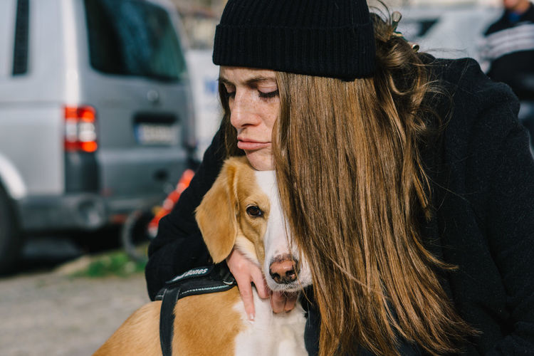 Midsection of woman with dog in car