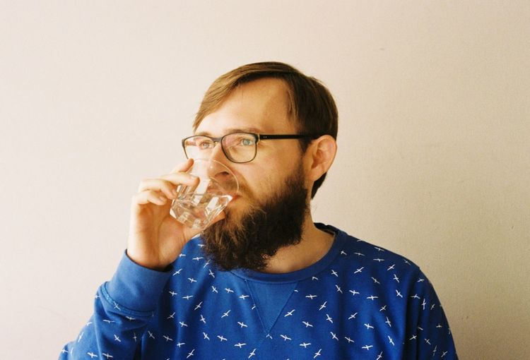 Bearded man drinking water against wall