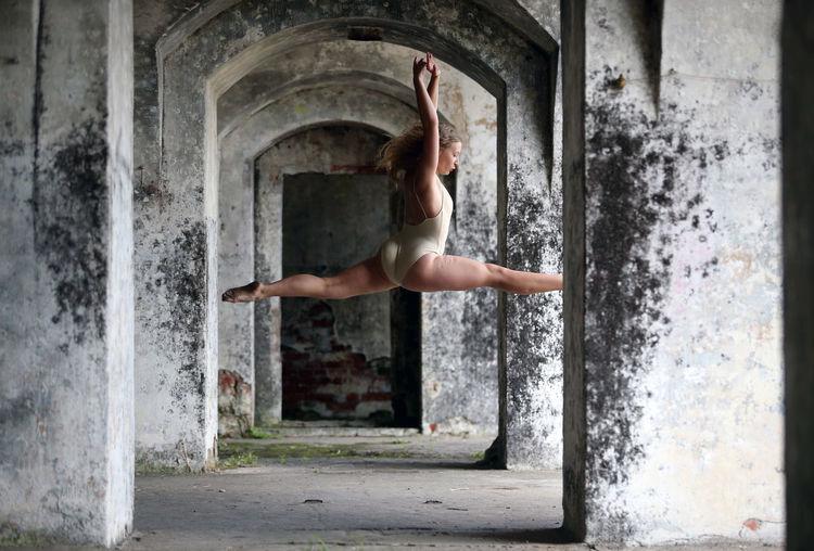 Full length of ballet dancer jumping against in abandoned building