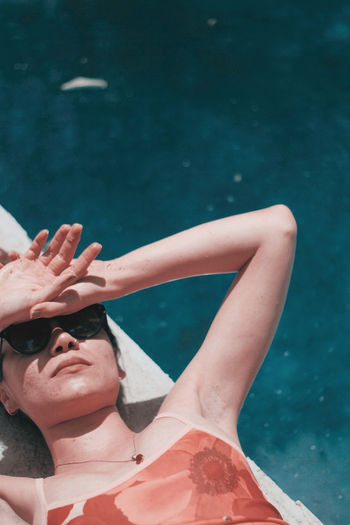 High angle view of woman wearing sunglasses lying at poolside