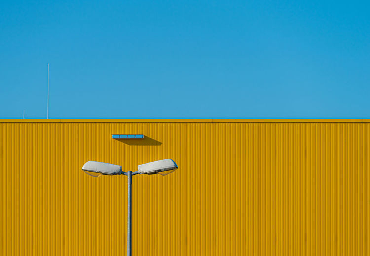 Low angle view of street light against yellow sky