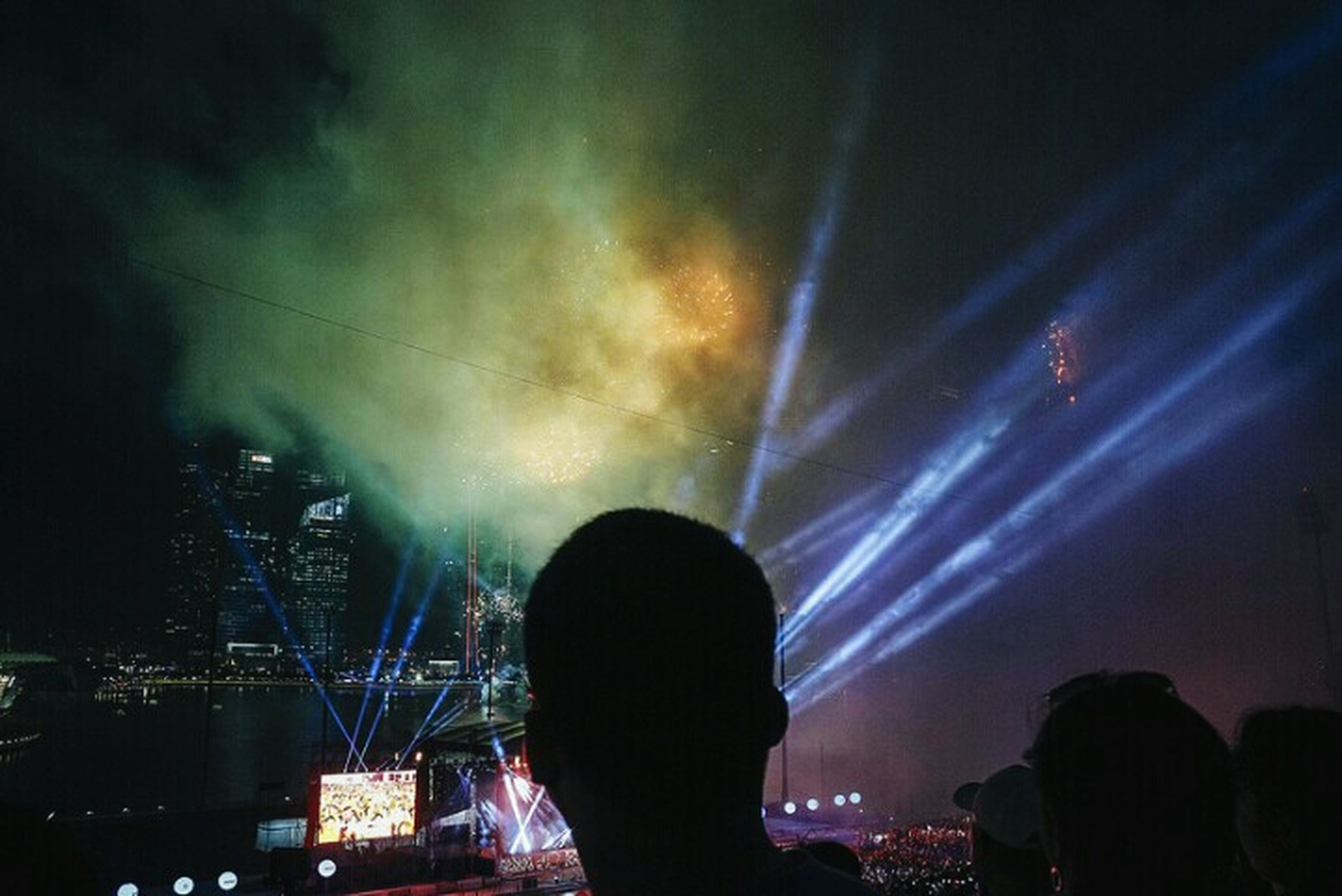 night, illuminated, silhouette, sky, lifestyles, arts culture and entertainment, men, leisure activity, lighting equipment, long exposure, event, light - natural phenomenon, nightlife, low angle view, rear view, light beam, unrecognizable person, dark