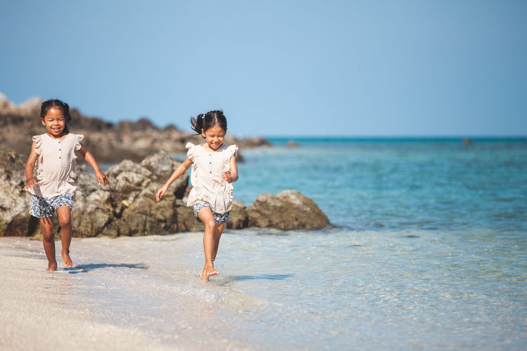 Full length of girls running at beach against clear sky