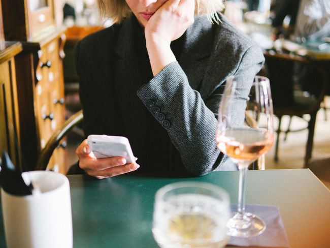 Communication Connection Day Drink Focus On Foreground Food And Drink Front View Holding Indoors  Lifestyles Midsection Mobile Phone One Person Portable Information Device Real People Restaurant Sitting Smart Phone Table Technology Using Phone Wireless Technology Women Young Adult Young Women