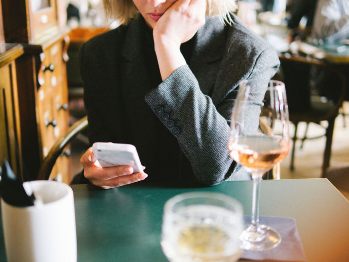 Midsection of woman using smart phone in restaurant