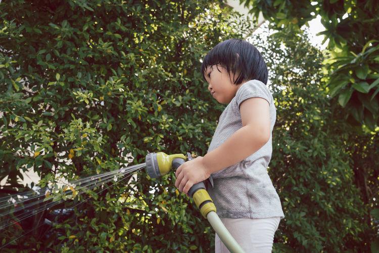 Cute girl holding garden hose outdoors