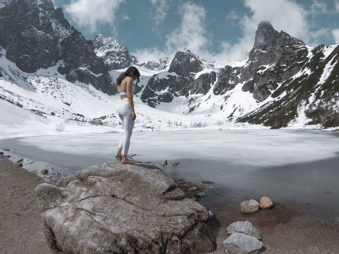 Woman standing on rock against mountains during winter