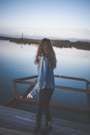 Woman standing on pier over lake against sky