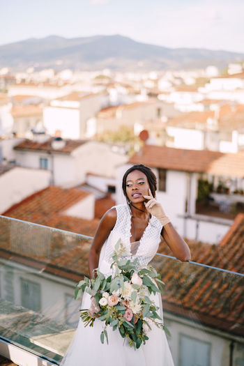 Smiling bride with bouquet standing against cityscape