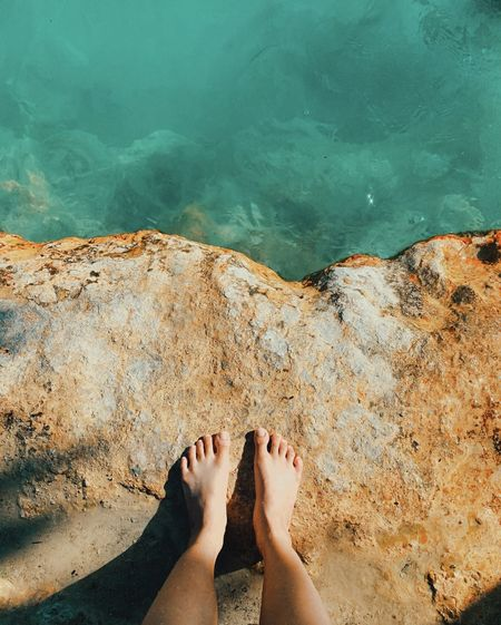 Low section of person on rock by swimming pool