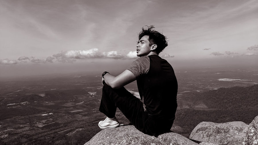 Side view of young man sitting on rock looking at landscape