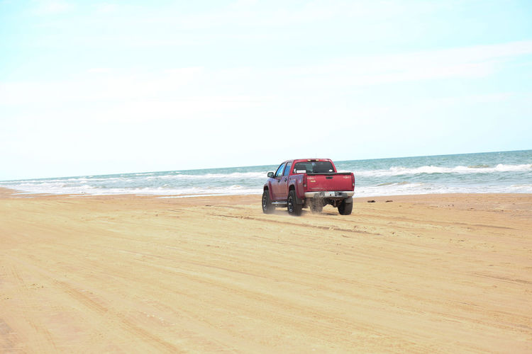 Pick-Up Truck Moving At Beach Against Clear Sky