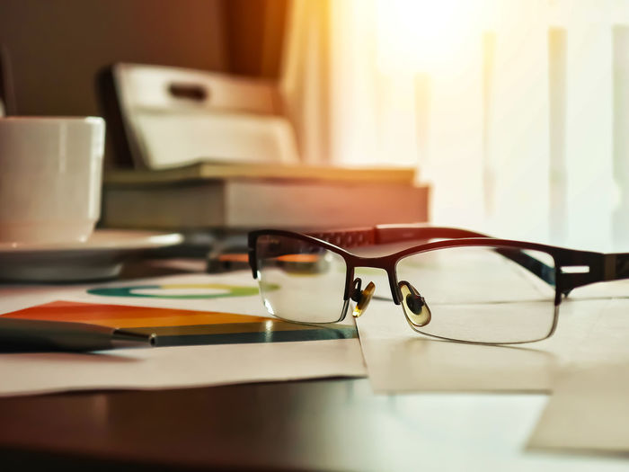 Close-up of eyeglasses with books and cup on table against window