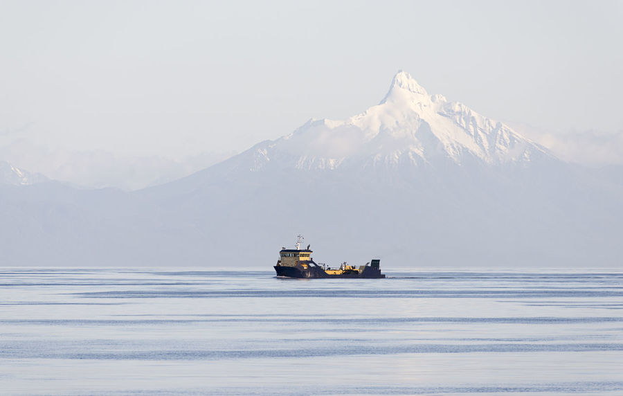 Big cargo boat with mountain with snow cap in ocean background Beauty In Nature Cold Temperature Day Glacier Mode Of Transport Mountain Mountain Range Nature Nautical Vessel No People Oil Pump Outdoors Sailing Scenics Sea Sky Snow Snowcapped Mountain Transportation Water Winter