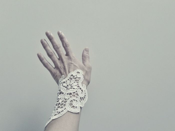Cropped image of woman hand with macrame bracelet against white wall