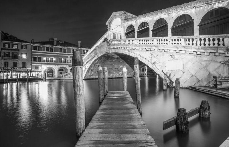 Jetty against rialto bridge over grand canal in city