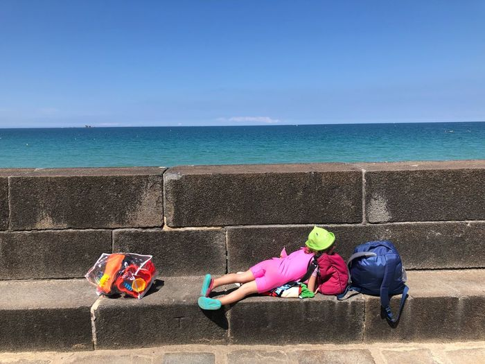 Girl Relaxing On Retaining Wall Against Sea