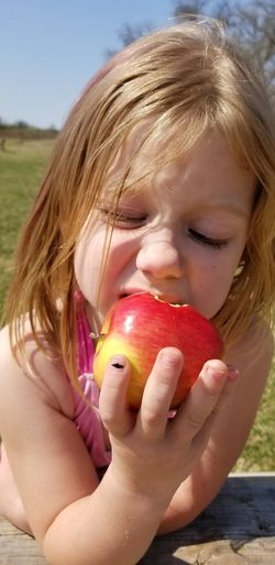 Close-up of girl eating apple outdoors