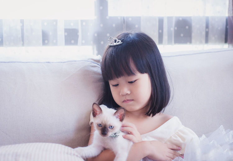 Cute girl with kitten sitting on sofa at home