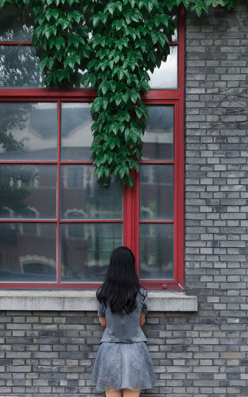 Rear View Of Woman Standing Against Window Of House