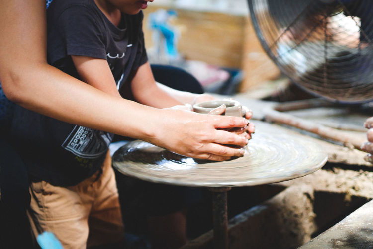 Midsection of people working on pottery wheel