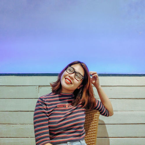 Portrait of smiling young woman standing against sky