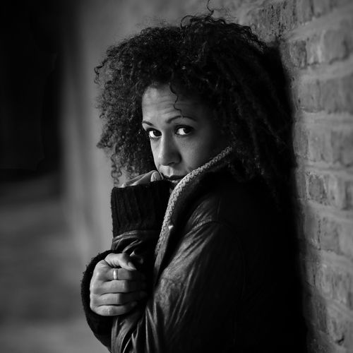 Portrait Of Mid Adult Woman In Jacket Standing Against Wall