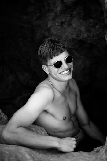 Portrait of smiling shirtless young man wearing sunglasses sitting by rock
