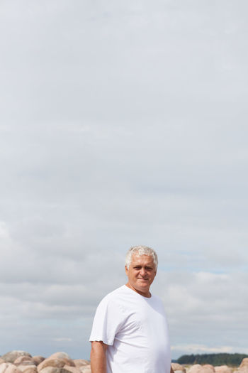 Portrait Of Mature Man Standing Against Sky