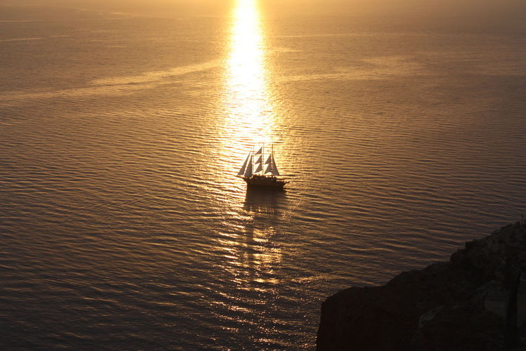 Silhouette boat in sea during sunset