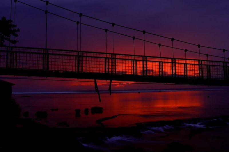Silhouette bridge over river against romantic sky at sunset
