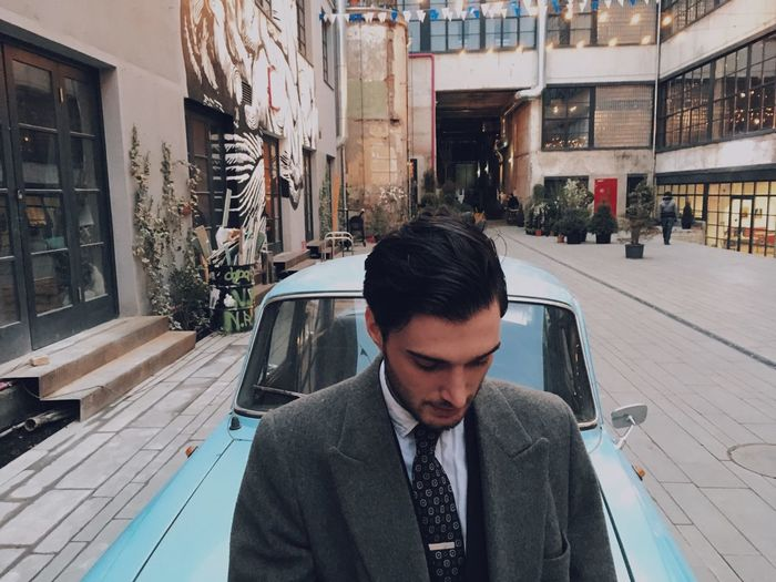 Man looking while standing against car in city