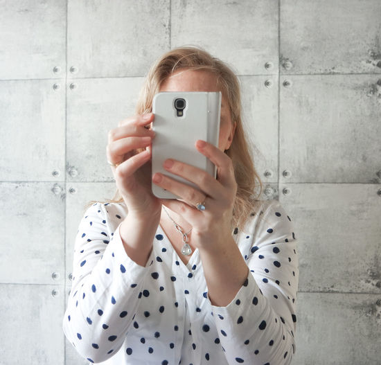 Woman clicking selfie through smart phone against wall at home