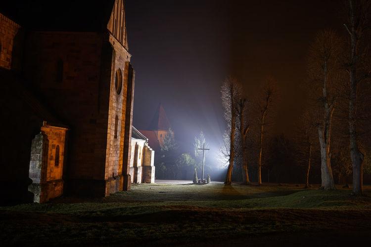 Bare trees on field by church at illuminated night