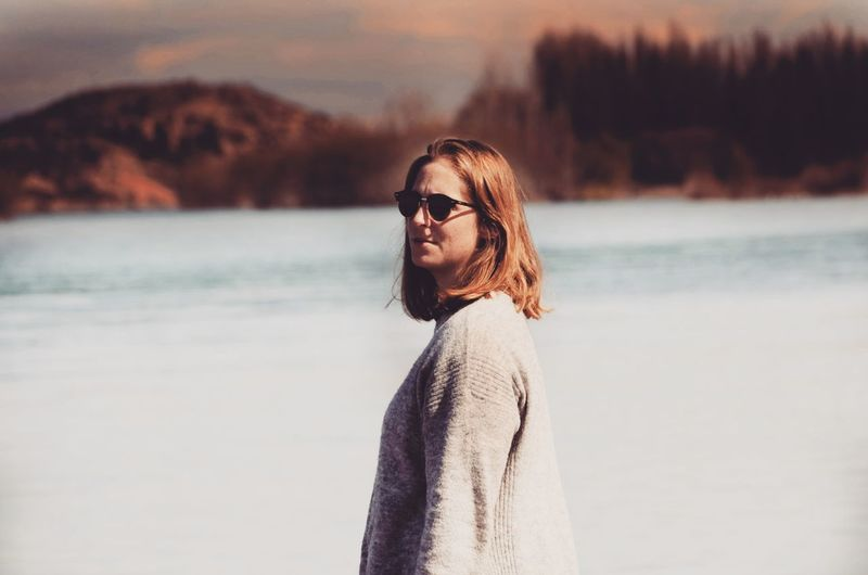 Portrait of young woman wearing sunglasses standing in sea