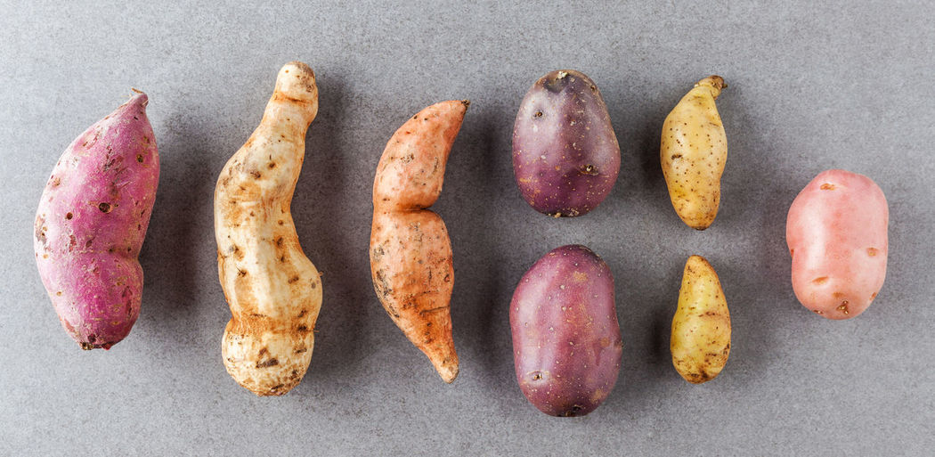 Different kinds of potatoes flat lay on stone surface. Close-up Day Directly Above Food Food And Drink Freshness Gray Background Healthy Eating High Angle View Indoors  No People Potatoes Raw Potato Studio Shot Sweet Potatoes