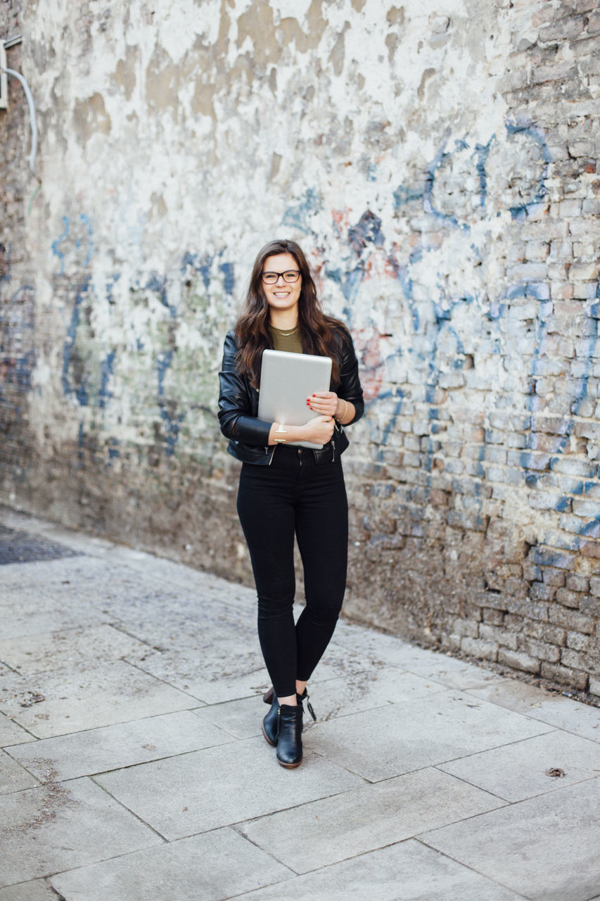 Portrait Of Smiling Young Woman With File Standing On Footpath