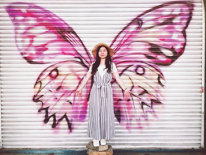 Portrait of woman standing against pink butterfly wings graffiti on closed shutter