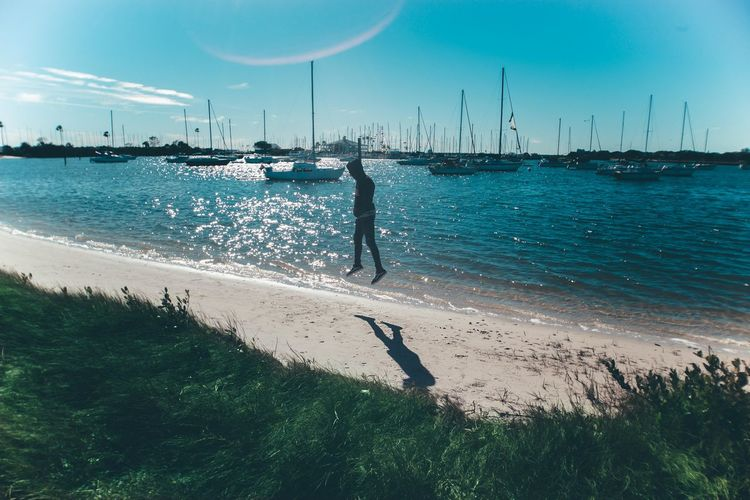 Scenic View Of Man Jumping On Beach