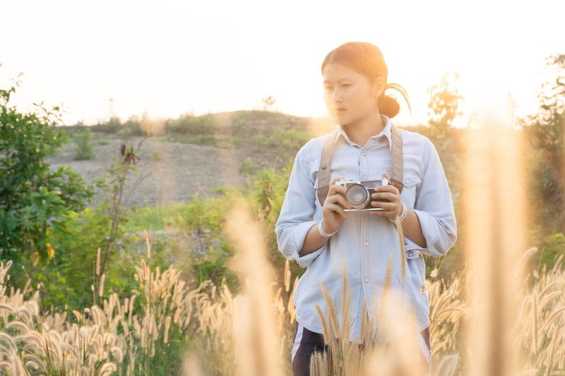 One Person Nature Three Quarter Length Sunlight Young Adult Sky Casual Clothing Plant Lifestyles Land Looking Sunset Day Front View Field Landscape Rural Scene Outdoors Leisure Activity