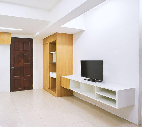Built-in furniture in the modern hotel apartment room with chair, mirror Apartment Architecture Building Built Structure Built-in Contemporary Decoration Decorative Design Domestic Room Flat Screen Flooring Furniture Home Home Interior Home Showcase Interior Hotel House Indoors  Living Room Modern No People Television Set Utility White Color
