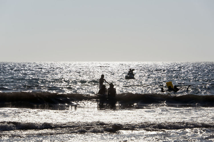 Silhouette of People playing, swimming in the waves in the island of Patmos, Greece in summer time Beach Beauty In Nature Clear Sky Day Horizon Horizon Over Water Land Leisure Activity Lifestyles Men Motion Nature Outdoors Real People Scenics - Nature Sea Sky Two People Water Wave
