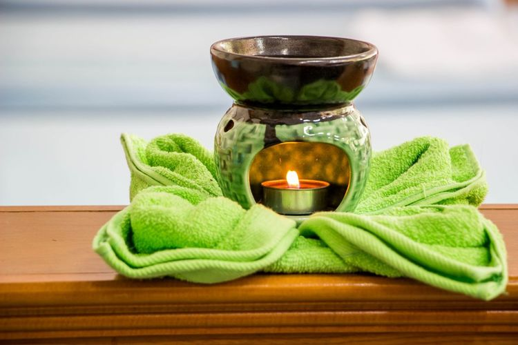 Close-up of tea light candle in vase and towel on table
