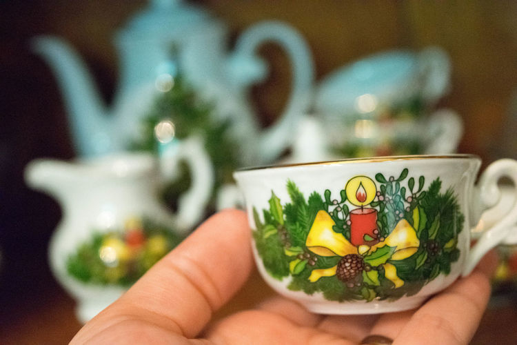 Cropped Image Of Hand Holding Antique Tea Cup